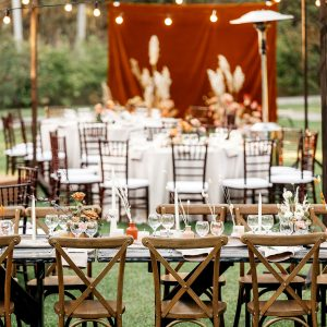 outside wedding reception venue wood chairs table wine glasses