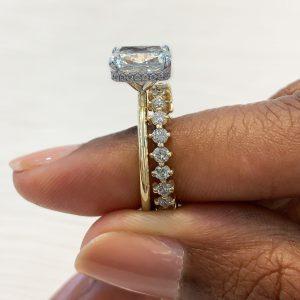 ladies hand holding yellow gold engagement ring diamond wedding band compass set round diamonds