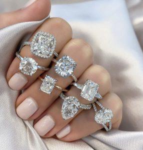 ladies hand multiple diamond moissanite white gold yellow gold halo pave diamond engagment rings